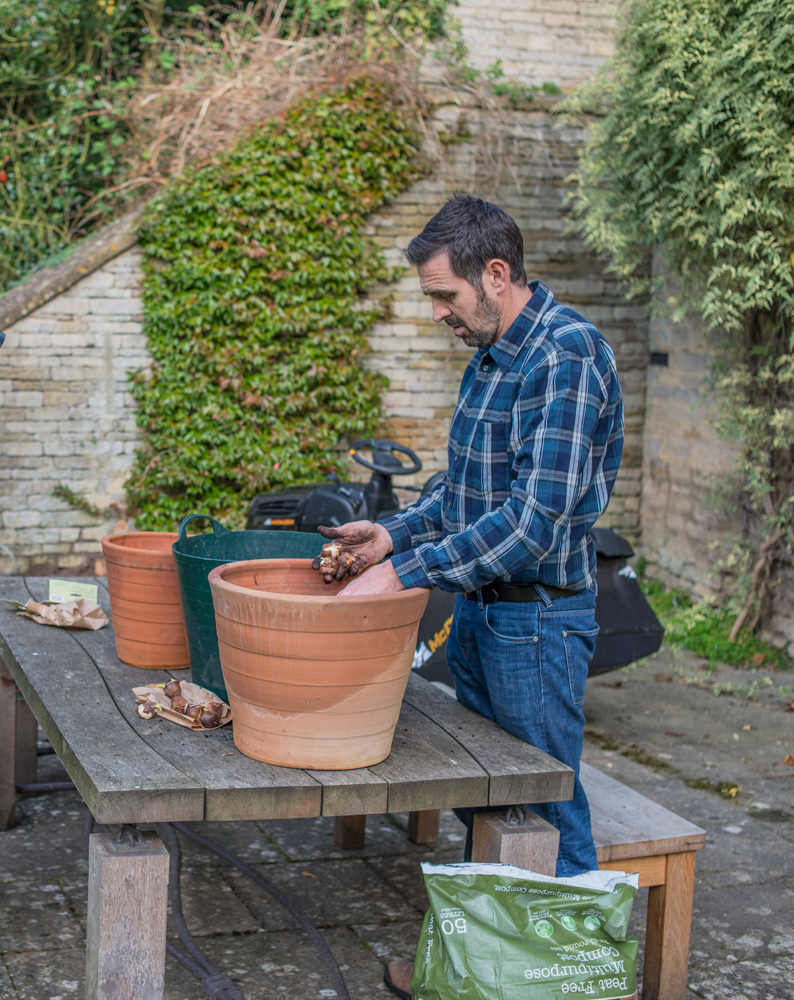 Adam Frost planting bulbs in containers in his garden