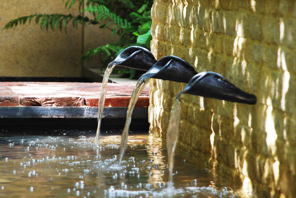 Three bespoke water spouts feeding a rill, designed by Adam Frost